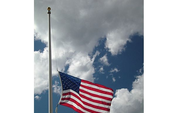 jc1217 montpelier vt vermont american flag flag pole flying half mast against a blue sky with white puffy clouds